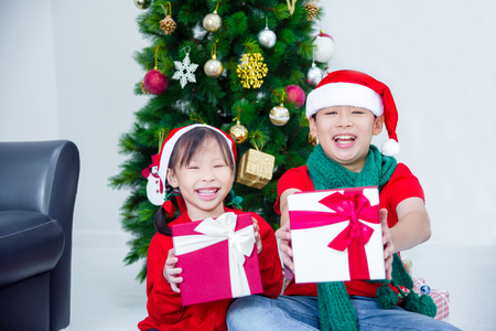 Young asian sibling,brother and sister holding present boxes and smiling together at home with Christmas decoration
