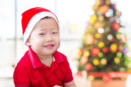 Little asian boy wearing red santa hat with red T-shirt smiling at camera in Christmas decoration room
