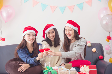 Three beautiful asian girls celebrating Christmas or the New Years Eve with wine