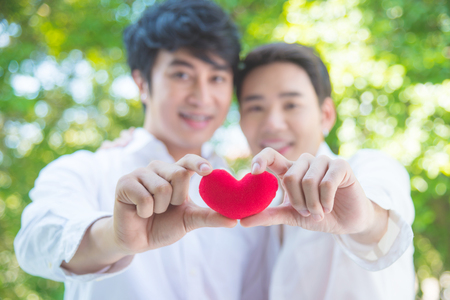Young asian homosexual couple holding red color heart shape and smile together Stock Photo