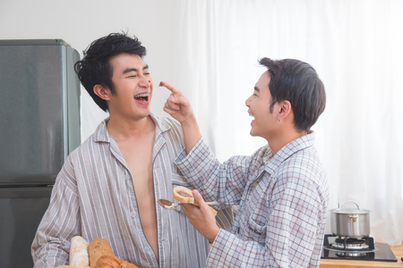 Young asian homosexual couple prepairing breakfast in kitchen together