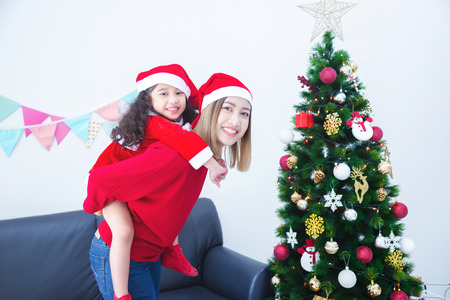 Beautiful asian mother and her daughter wearing christmas costume and smiling in room with Christmas tree decoration
