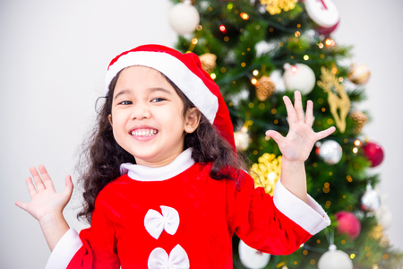 Little asian girl wearing christmas costume and smiling in room with Christmas tree decoration Stock Photo