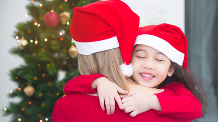 Little asian girl hugging her mother and smile on Christmas day