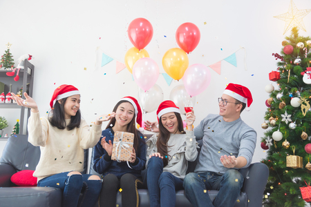 Three beautiful asian girls and a man celebrating Christmas or the New Years Eve party
