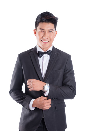 Portrait of young asian confident man dressed in tuxedo with bow tie isolated on white background