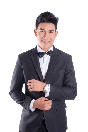 Retrato de joven asiático confiado vestido con esmoquin con pajarita aislado sobre fondo blanco.