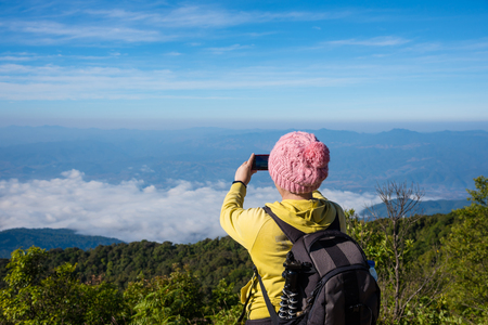 Middle aged female hiker taking photo of beautiful morning view in the mountains by smartphone