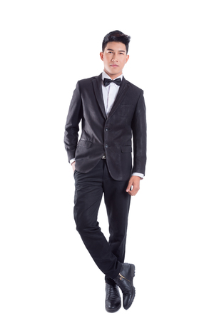 Portrait of young asian confident man dressed in tuxedo with bow tie isolated on white background Foto de archivo
