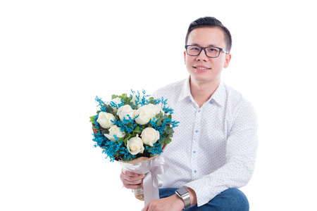 Portrait of young asian man holding flowers isolated on white background Stock Photo