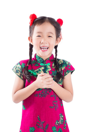 Little asian girl in traditional chinese costume smiling over white background