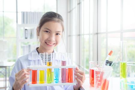 Niña de la escuela asiática joven de pie y sonríe en el aula de química, concepto de educación. Foto de archivo