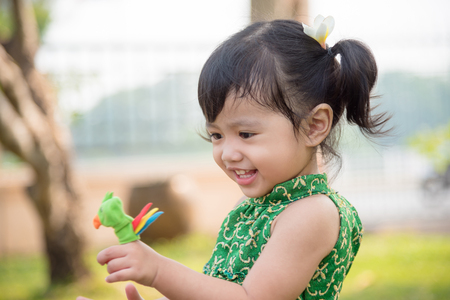 Little asian girl playing finger puppet and smiles in park