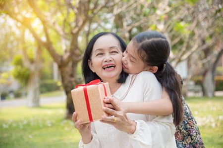 Asiatische Enkelin, die Geburtstagsgeschenk für Enkelin im Garten gibt. Glückliche asiatische Familienkonzeption.