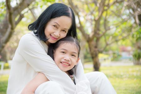 아시아 할머니와 손녀가 함께 정원에 앉아 있습니다. 행복한 아시아 가족 개념입니다.
