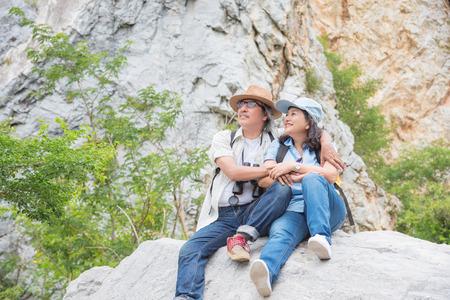 Azjatycki starszy para siedzi na skale w górach razem, podróżując na wycieczce emerytalnej. Zdjęcie Seryjne