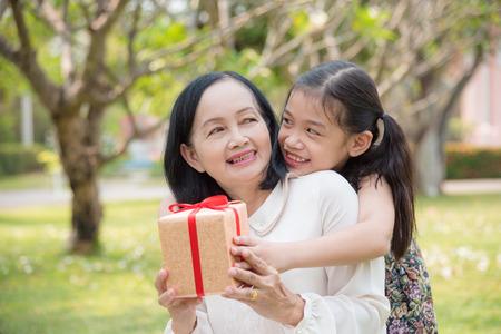 Aziatische kleindochter die verjaardagscadeau geeft voor kleindochter in de tuin. Gelukkige Aziatische familieconceptie.