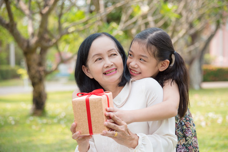 Azjatycka wnuczka dając prezent urodzinowy dla wnuczki w ogrodzie. Szczęśliwe azjatyckie poczęcie rodziny.