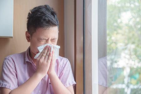 Zieke aziatische jongen die neus in weefsel blaast, ongezond kind dat lijdt aan een loopneus of niest en zijn neus en mond bedekt met papieren zakdoekje. Stockfoto