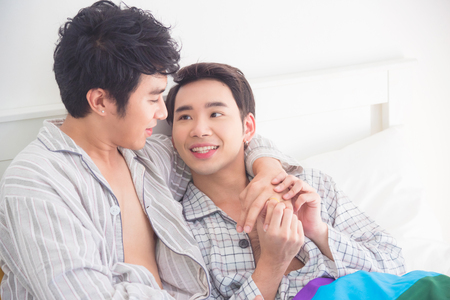 Young Asian Gay couple wearing pajamas lying on the bed together at home,Homosexual couple concept.