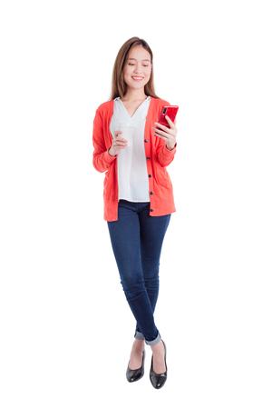Longitud total de hermosa mujer asiática sosteniendo teléfono inteligente y taza de café aislado sobre fondo blanco.