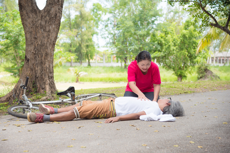Asian female wife First Aid Emergency on Heart Attack senior male husband with cardiac arrest while exercise in park. Basic life support ,People concept Standard-Bild