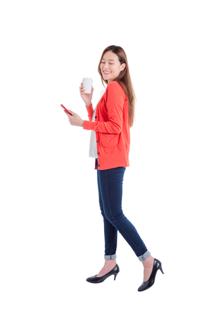 Full length of beautiful asian woman holding smart phone and coffee cup isolated over white background Stockfoto