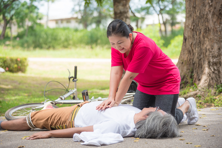Asian female wife First Aid Emergency CPR on Heart Attack senior male husband with cardiac arrest while exercise in park. Basic life support ,People concept