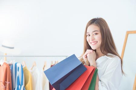 Piękna kobieta Azji gospodarstwa torby na zakupy i uśmiecha się w sklepie odzieżowym odzieżowym. Sprzedaż, koncepcja zakupów.