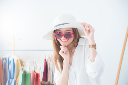 Beautiful asian woman trying sunglasses and hat at a shop in shopping center. Sale and shopping concept. 免版税图像