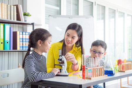 Mooie Aziatische vrouwelijke leraar die studenten lesgeeft in de schoolbibliotheek