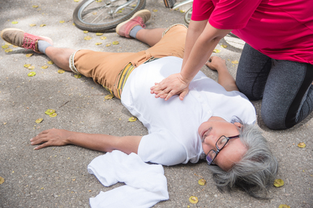 Hand of Asian Woman First Aid Emergency CPR on Heart Attack Senior senior man with cardiac arrest while exercise in park. Basic life support concept .