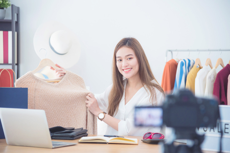 Beautiful asian woman blogger showing clothes in front of camera to recording vlog video live streaming at her shop.Business online influencer on social media concept.