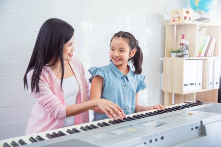 Beautiful asian pianist teacher teaching a girl to play piano, music education concept.