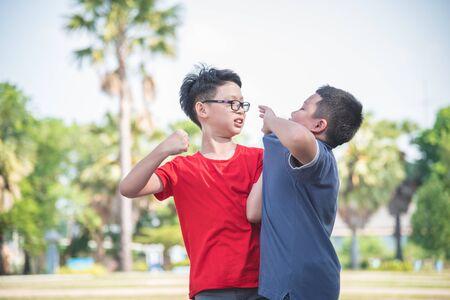 Scolaro asiatico vittima di bullismo, bambini che combattono con un compagno di classe nel parco della scuola. Bullismo e violenza nel concetto di scuola.