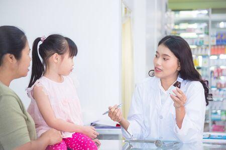 Belle pharmacienne asiatique expliquant le médicament au patient en pharmacie