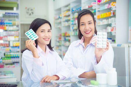 Dos mujeres asiáticas farmacéutico sosteniendo la medicina y la sonrisa en la farmacia (farmacia o droguería) Foto de archivo