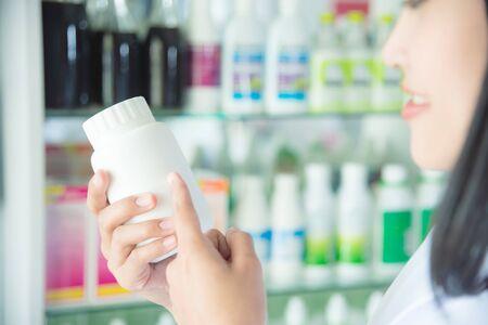 Smiling asian female pharmacist holding and pointing medicine bottle in drugstore
