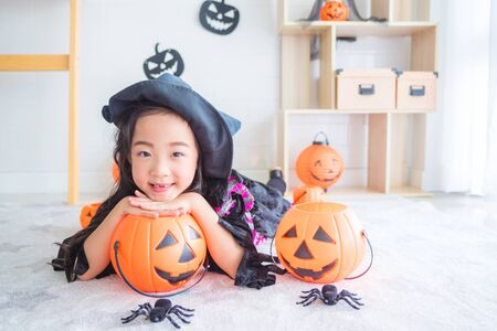 Little asian girl in witch costume lying on the floor in room decorated for Halloween day