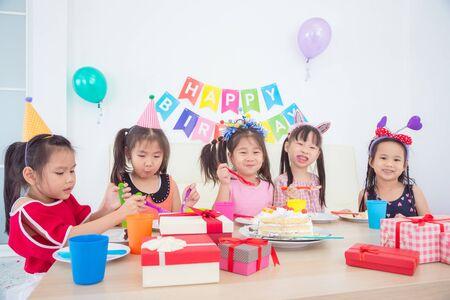 Gruppe asiatischer Kinder, die auf Geburtstagsfeier Kuchen mit einem Lächeln essen Standard-Bild
