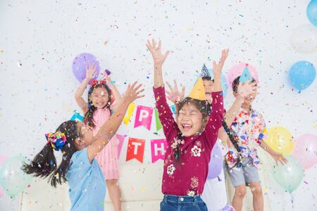Happy Asian Girl Enjoy Throwing Colorful Confetti with Friends in Birthday Party