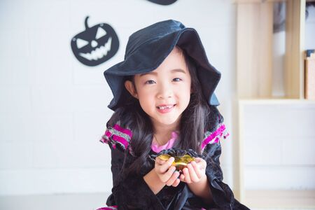 Little asian girl in halloween witch costume sitting and holding chocolate with smile