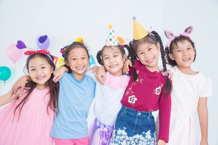 Group of adorable asian girls having fun at birthday party