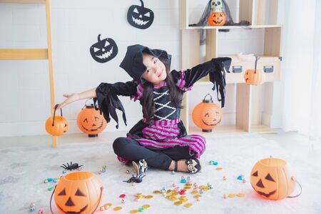 Little asian girl in witch costume sitting in room decorated for Halloween day Imagens