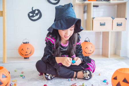 Little asian girl in halloween witch costume sitting on the floor and eating chocolate in room decorated for Halloween's day