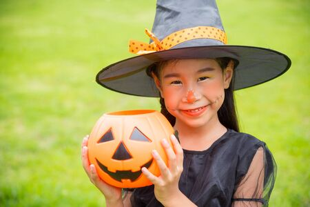 Little asian girl in witch costume celebrate Halloween outdoor, holding pumpkin bucket and smiles. 写真素材