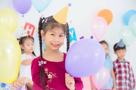 Little pretty girl holding balloons and smiles in birthday party with friends