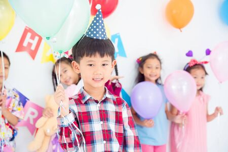 Little asian boy holding balloons and smiles in birthday party with friends