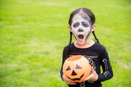 Little asian girl in bone devil costume celebrate Halloween outdoor.