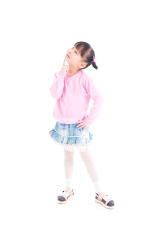 Little asian girl standing  and looking up with smiles over white background 写真素材